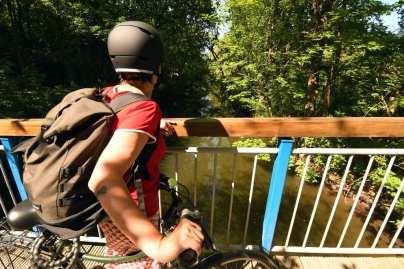 Frau mit Fahrradhelm und Fahrrad schaut von einer Brücke auf einen Fluss
