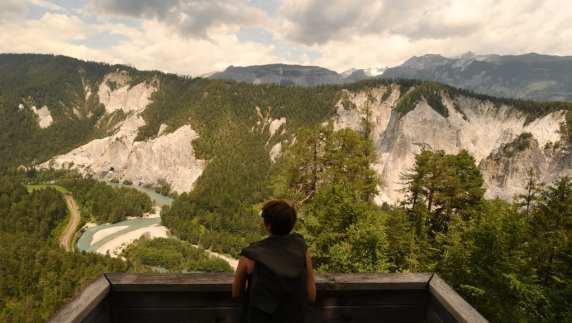 Frau schaut von Aussichtspunkt auf eine Schlucht