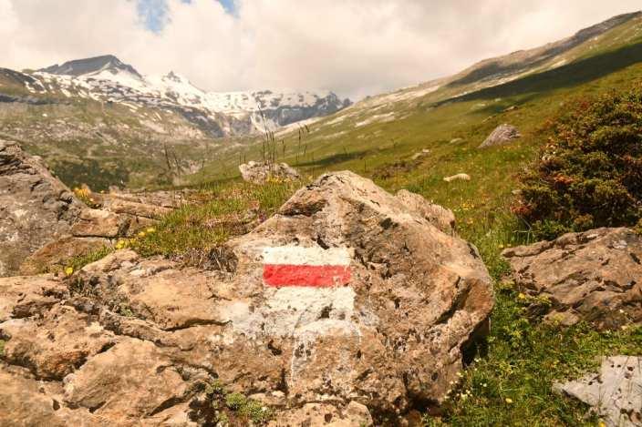 Wandermarkeirung an einem Felsen, dahinter schneebedeckte Berge