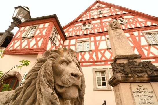 Fachwerkhaus, davor eine Löwenstatue
