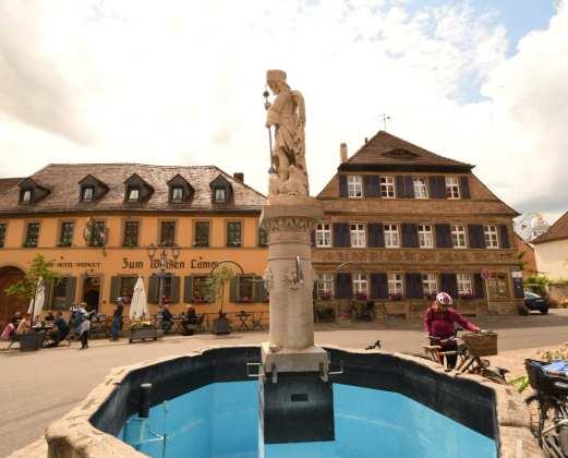Brunnen vor einem Gasthof in einer schönen Altstadt