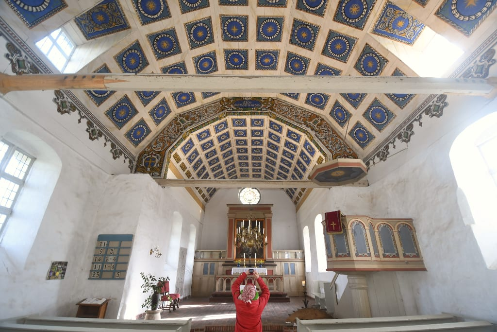Frau fotografiert Decke einer Kirche
