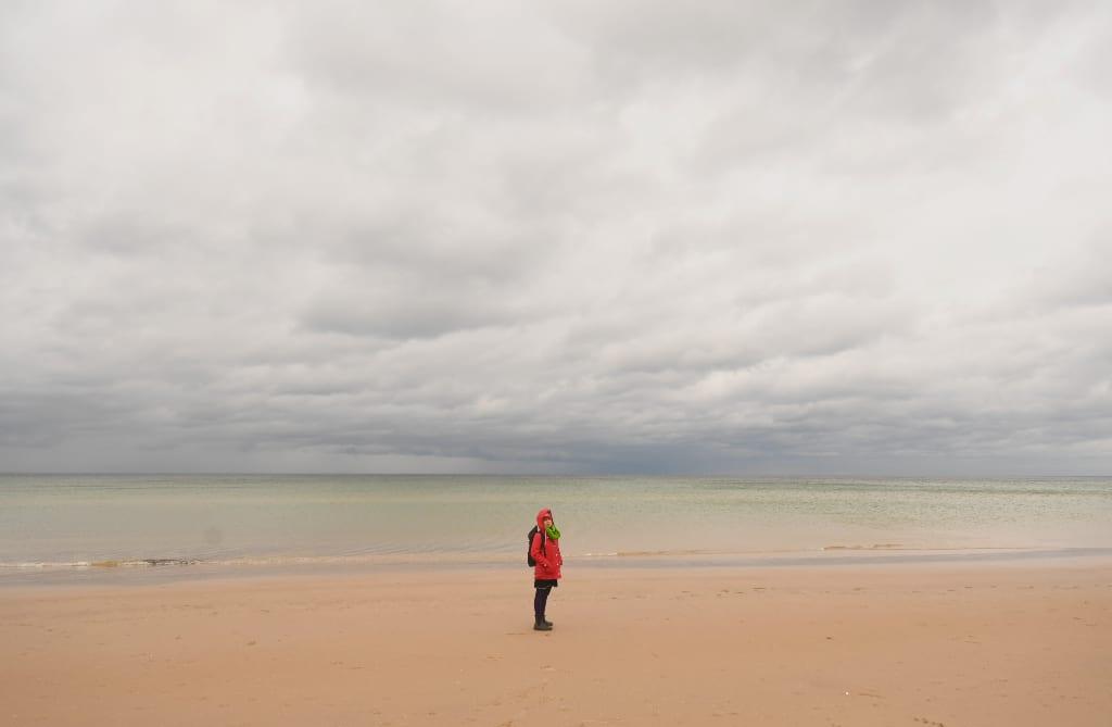 Frau steht auf leerem Winterstrand