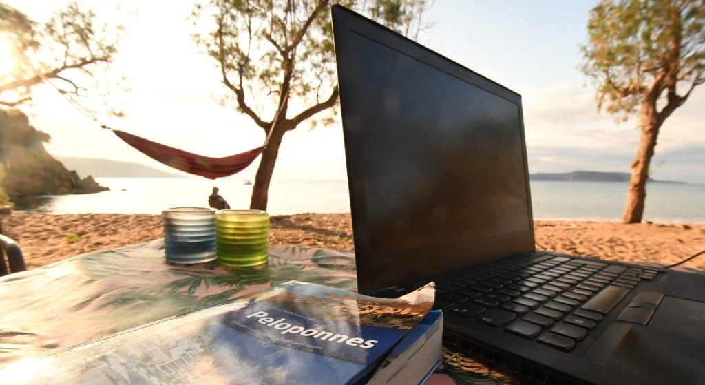Laptop und reiseführer an einem Strand