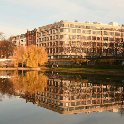 Gebäude mit vielen Fenstern spiegelt sich im Wasser
