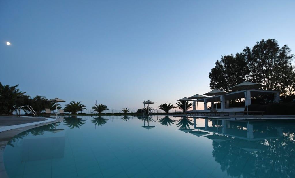Pool mit Palmen im Abendlicht