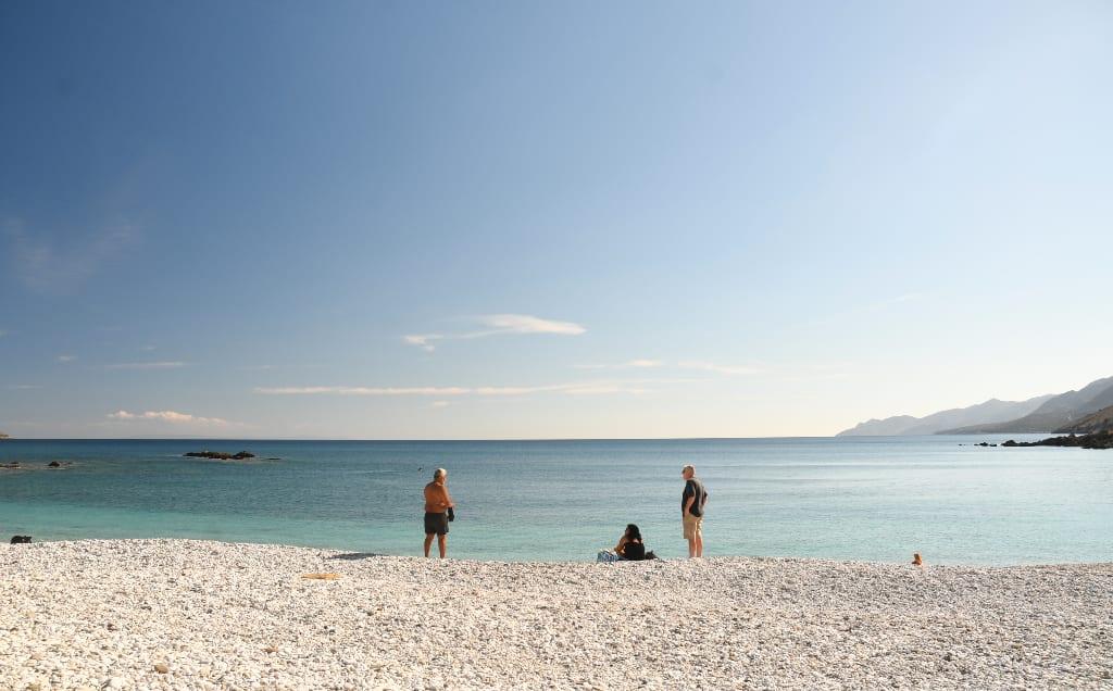Weißer Kieselstrand am türkisblauen Meer