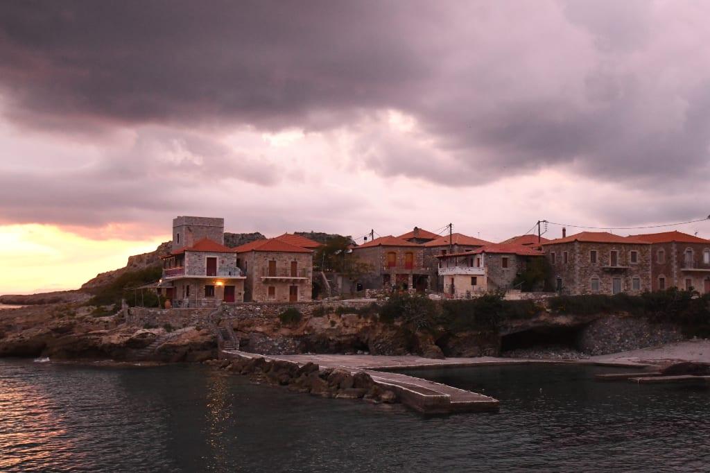 Wolken und Sonnenuntergang über einem Dorf am Meer