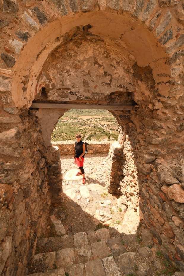 Frau steht in Ruinen
