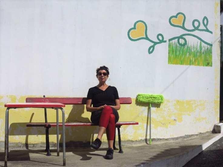 Frau sitzt vor Wand mit Herzen