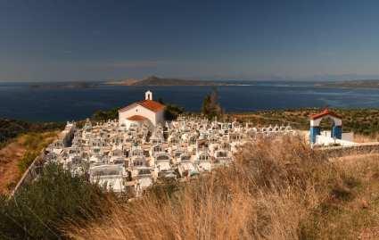 Friedhof mit weißen Kreuzen, dahinter das Meer