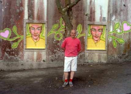 Mann steht vor Porträtgemälden an einer Wand