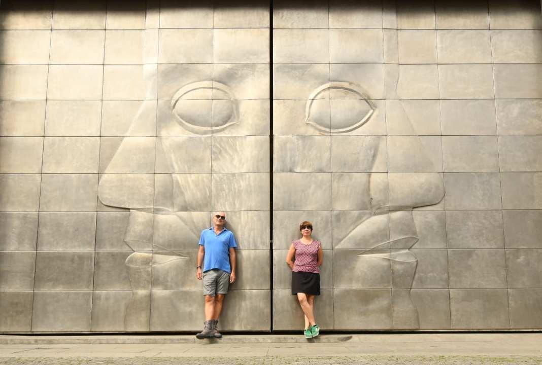 Frau und Mann vor Metalltür mit eingestanztem Gesicht
