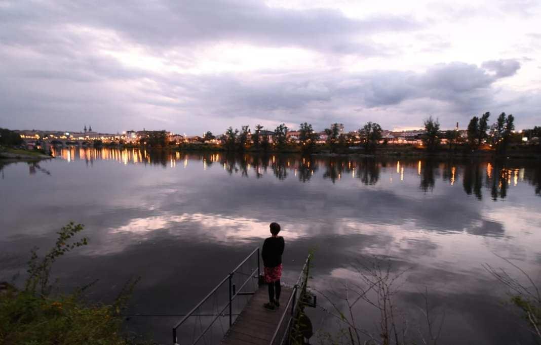 Frau blickt über einen Fluss hinweg