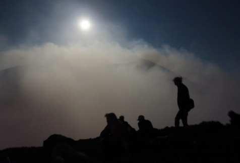Silhouette von Menschen, dahinter Rauch und Mond