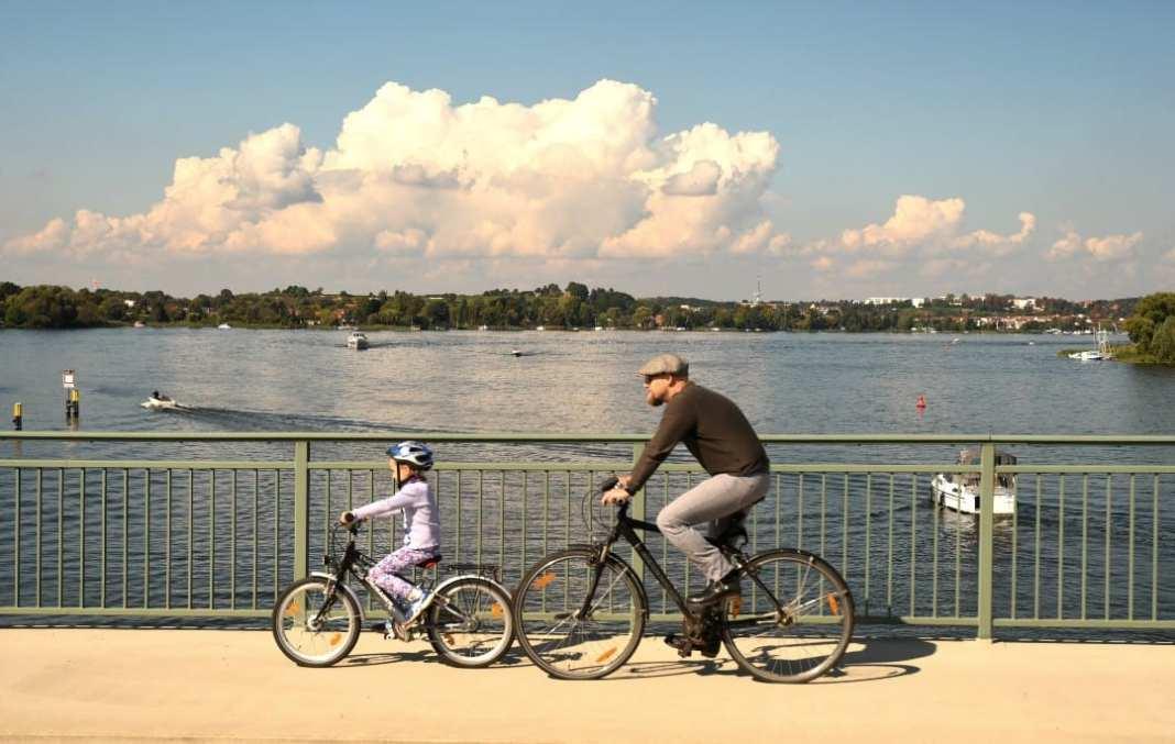 Mann mit Kind fahren Fahrrad auf einer Brücke