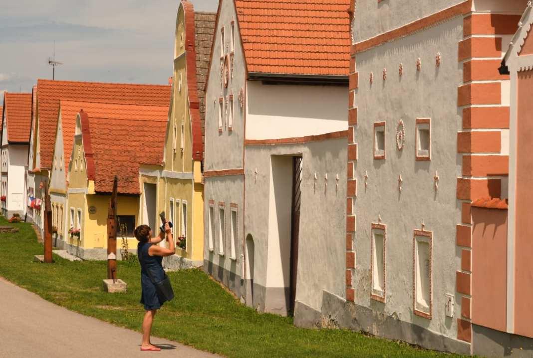 Frau fotografiert Häuserfassade in einem Dorf