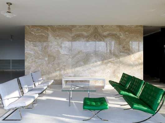 Onyxwand mit grünen Stühlen davor