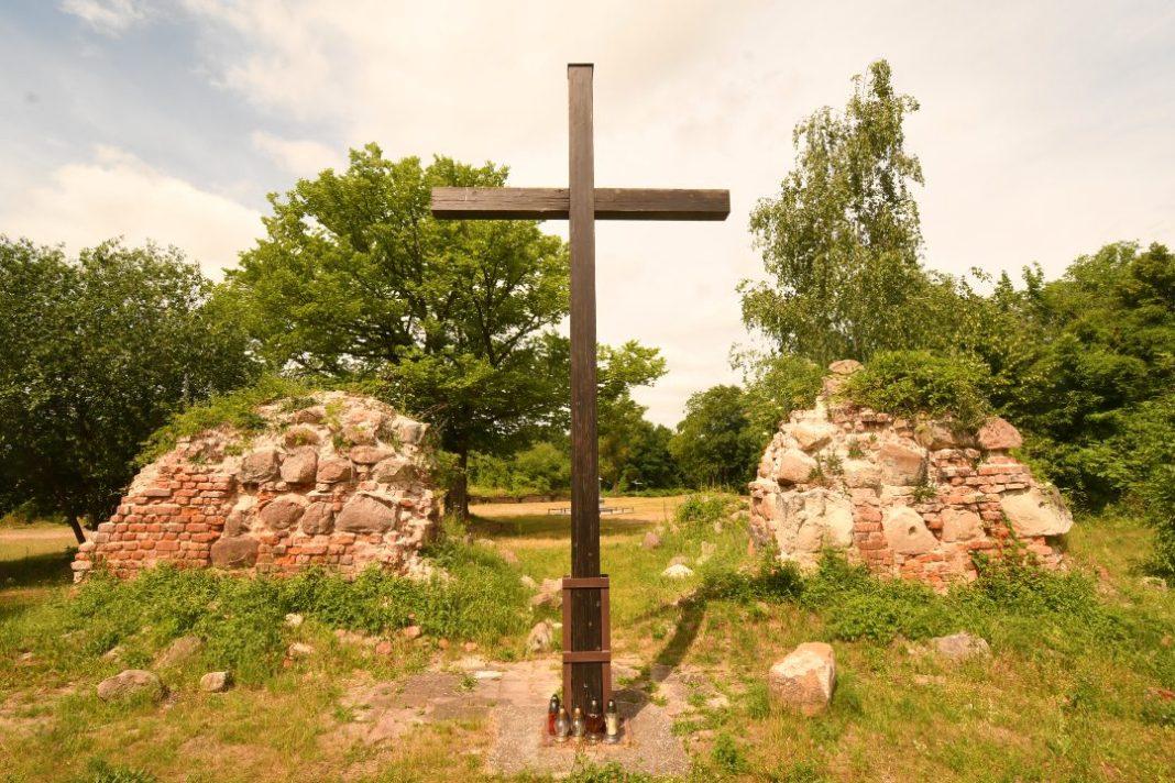 Holzkreuz vor Ruinen