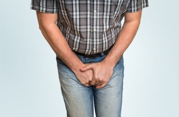 Man holding crotch area because of Urinary Incontinence from Prostate Cancer