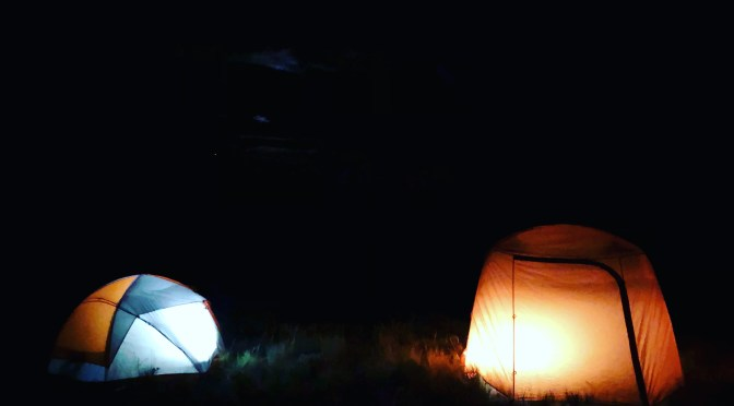 two tents lit from the inside, glowing in the dark night