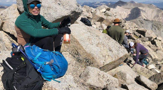 Hikers rest next to their backpacks atop the rocky summit of Colorado fourteener Mt. Shavano