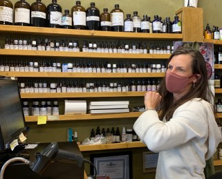 Dr. Nearpass, a woman in a white hoodie, long brunette hair, and a maroon mask, stands in front of a wall of shelves of naturopathic medicine in brown glass jars with black lids at the Backcountry Apothecary in Frisco, CO.