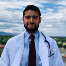 Image of Jesse Santana, dark brown hair, brown skin, beard and moustache with a stethoscope draped over his white coat, striped, collared shirt and maroon tie.