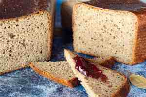 image of sliced all the grains sourdough loaf with jam