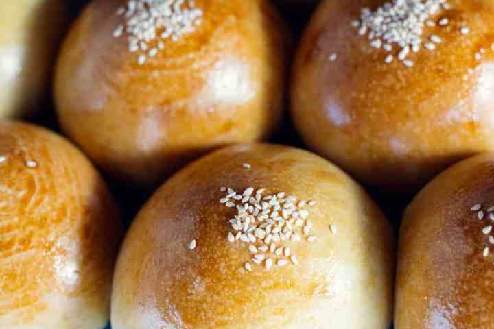 image of close up baked sourdough red bean buns recipe with sesame seeds