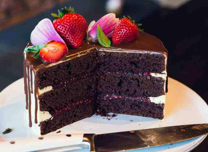 image of sliced chocolate cake with raspberry filling, vanilla frosting, and chocolate ganache drip with strawberries and magnolia flowers on top