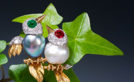 An amusing gem-set bird brooch by Cartier designed as two birds perched on a branch. The bodies set with grey and white pearl, the diamond-set heads with emerald and ruby eyes, the textured feathers with diamond details, mounted in platinum and 18 karat gold. Signed 'Cartier, Paris' and numbered Paris, circa 1950