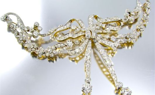 A Belle Époque Tiffany & Co. platinum topped 18 karat yellow gold stomacher brooch. Circa 1900. Signed Tiffany & Co. The stomacher is of typical form, designed with scrolling and foliate diamond set pendant sides, centering a diamond set stylized ribbon tied bow.