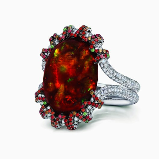Martin Katz white gold ring featuring a central 13.18ct fire opal cabochon, micro-set with diamonds, tsavorite garnets and orange-red sapphires.