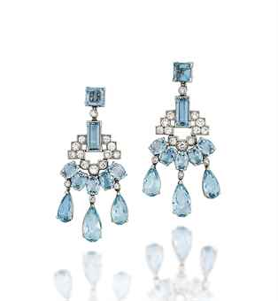 A PAIR OF ART DECO AQUAMARINE AND DIAMOND EAR PENDANTS, BY CARTIER (estimate £20,000 – £25,000). Each composed of a single square-cut aquamarine surmount, to a rectangular-cut aquamarine spacer and brilliant-cut diamond geometric design panel, with adjoining fan of oval-cut aquamarine accents, suspending three graduated pear shaped aquamarine drops, circa 1935, 5.2cm long, case, screw fittings.