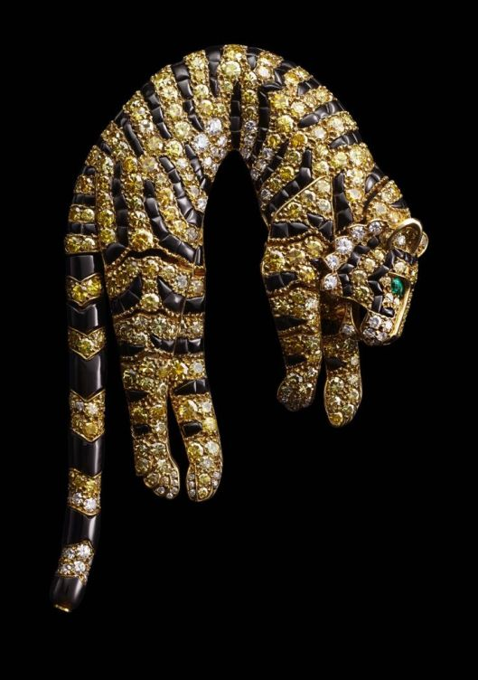 Tiger Clip Brooch, Cartier Paris, 1957. Yellow gold. Single- and brilliant-cut diamonds ranging from fancy intense yellow to near colorless. Marquise-shaped emeralds (eyes). Fancy-shaped onyx (stripes).