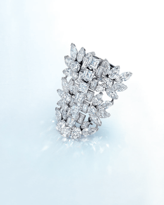 A DIAMOND BROOCH, BY CARTIER Designed as an openwork shield shape plaque, centering upon a line of rectangular and baguette-cut diamonds, flanked by old European and marquise-cut diamonds, mounted in platinum.