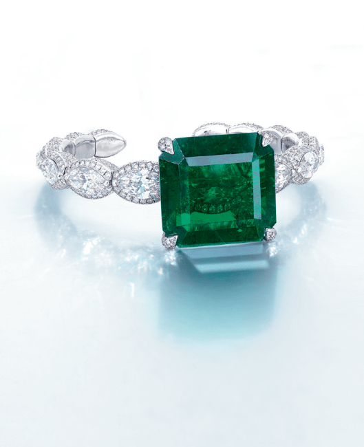 A STUNNING EMERALD AND DIAMOND BANGLE, BY ETCETERA The octagonal-shaped emerald weighing approximately 38.51 carats, to the brilliant-cut diamond prongs and gallery, extending to the hoop designed as a line of marquise-cut diamonds, six marquise-cut diamonds weighing from approximately 1.54 to 1.00 carats, mounted in 18k white gold.