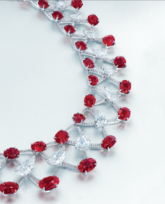 A magnificent ruby and diamond necklace by Etcetera. Designed as an articulated brilliant-cut diamond lattice-work band, centering on a line of graduated pear-shaped diamonds, thirteen pear-shaped diamonds weighing approximately 5.14 to 1.00 carats, framed by two rows of oval and cushion-shaped rubies weighing approximately 7.02 to 1.10 carats, to the brilliant-cut diamond link backchain accented with a pear-shaped diamond, mounted in 18k white gold.