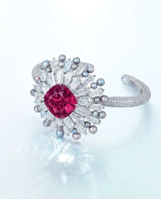 AN UNUSUAL SPINEL, DIAMOND AND PEARL BANGLE, BY FORMS Of starburst design, set to the centre with a cushion-shaped purplish-pink spinel weighing approximately 17.51 carats, within a radiating hexagonal-shaped diamond surround with round grey pearls, the reverse further embellished by hexagonal-shaped diamonds, joined to the pavé-set brilliant-cut diamond hinged band, mounted in 18k white gold.