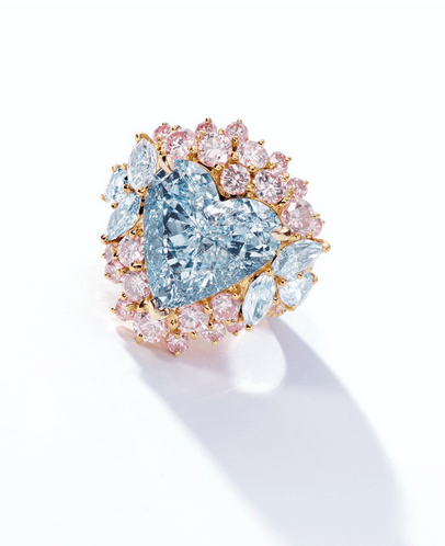 Centring on a heart-shaped fancy blue diamond weighing 7.02 carats, flanked by marquise- and pear-shaped blue diamonds, to a stylized mount set with brilliant- and circular-cut pink diamonds, the blue and pink diamonds together weighing approximately 3.60 carats, mounted in 18 karat pink gold.
