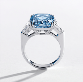 Centring on a square emerald-cut fancy vivid blue diamond weighing 8.01 carats, flanked on each side by a shield-shaped diamond together weighing approximately 1.00 carats, mounted in platinum.