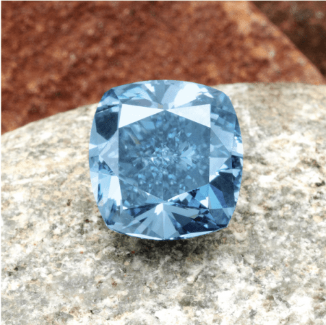 The fancy vivid blue modified rectangular brilliant-cut diamond weighing 7.03 carats, on a plain platinum mount. Illustrated unmounted.