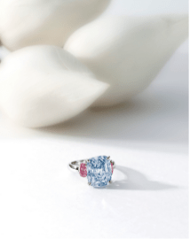 Centring on a cushion-shaped fancy vivid blue diamond weighing 6.01 carats, flanked on each side by an oval pink diamond weighing 0.46 and 0.44 carat respectively, mounted in platinum.