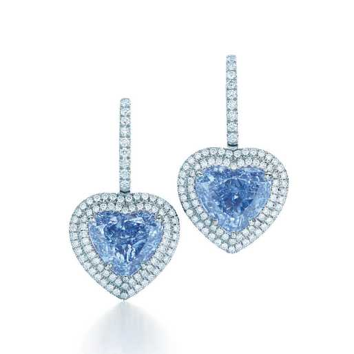 Exceptionally rare, a matched pair of heart-shaped Fancy Vivid Blue diamonds is set in platinum and surrounded by round brilliant white diamonds. Blue diamonds, carat total weight 3.84, clarity grades VVS1 and VS2; white diamonds, carat total weight .66.
