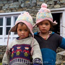 Two children in their matching hats between Koshigaun village and Phakding
