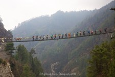 A large group of trekkers make a bridge crossing at Jorsalle.