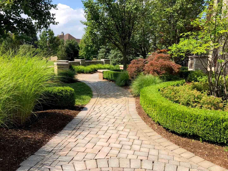 Neatly trimmed shrubs, ornamental grass, and perennials create an interesting garden along a pathway