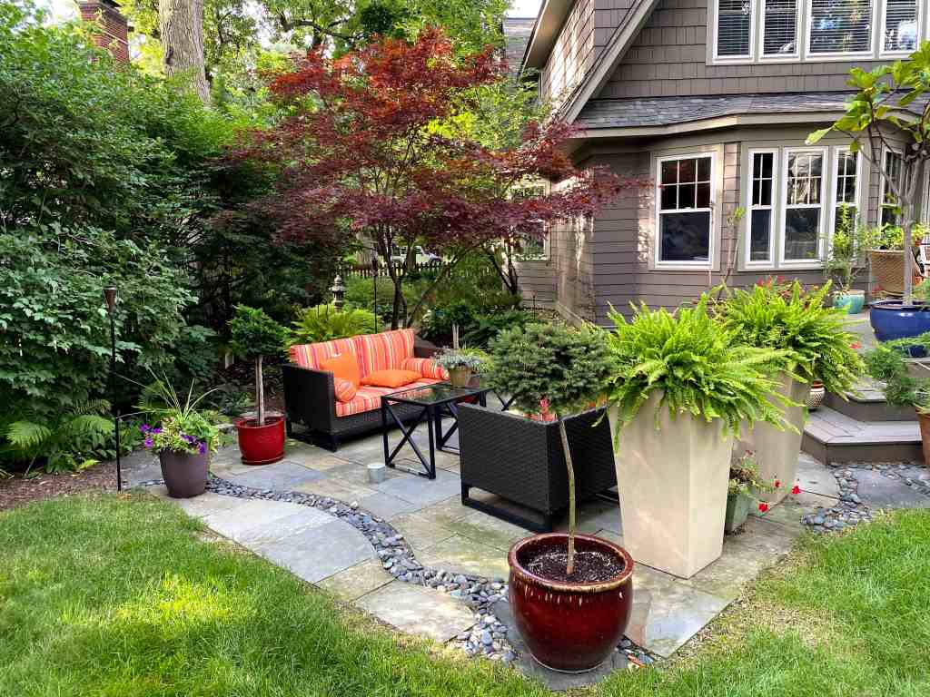Container gardens and a seating area adds a cozy space to a vibrant garden