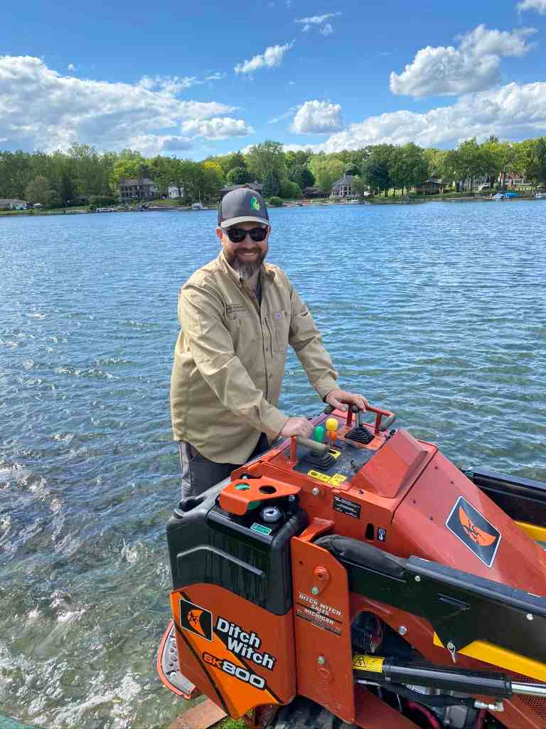 Jeff Kin using machinery called a Ditch Witch as he improves a clients property on a lake.